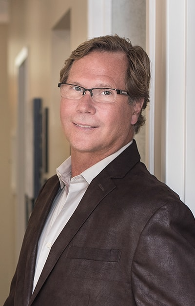 Dr. John Merrill, a Huntersville cosmetic dentist, smiling wearing a brown suit and glasses