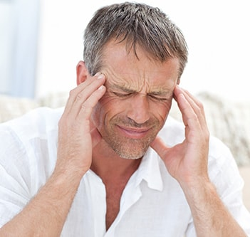 A man suffering from headaches and TMJ