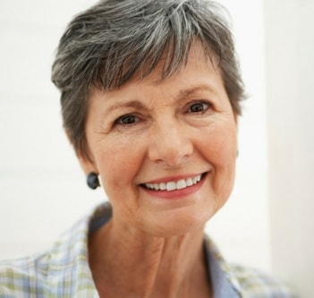 A woman with strong, healthy teeth and dental implants