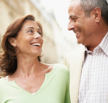 Couple smiling at each other who enjoy preventative and restorative dental services