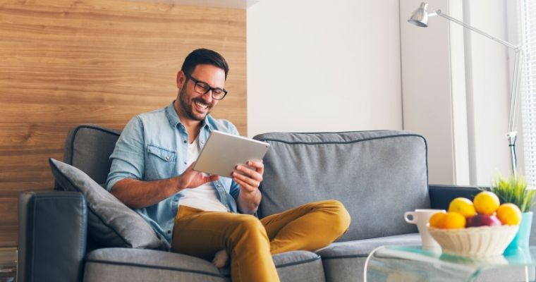 A man holding an iPad on a couch with his virtual dentist consultation
