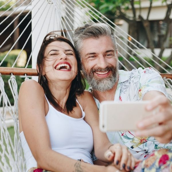 A happy couple with straight teeth taking a selfie on hammock